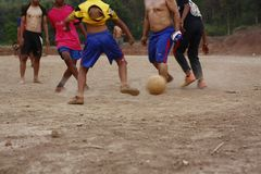 Teams of teenage and young boys playing soccer. Football on a dusty dirt field, evening time in Northern Thailand, Southeast Asia royalty free stock photography