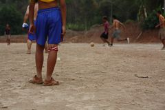 Teams of teenage and young boys playing soccer. Football on a dusty dirt field, evening time in Northern Thailand, Southeast Asia stock photo