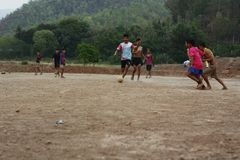 Teams of teenage and young boys playing soccer. Football on a dusty dirt field, evening time in Northern Thailand, Southeast Asia royalty free stock photos