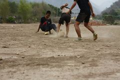 Teams of teenage and young boys playing soccer. Football on a dusty dirt field, evening time in Northern Thailand, Southeast Asia stock images
