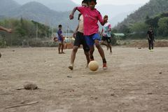 Teams of teenage and young boys playing soccer. Football on a dusty dirt field, evening time in Northern Thailand, Southeast Asia stock photos