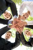 Teamwork. Bottom view of people making pile of hands on background of green foliage stock photography