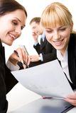 Teamwork. Portrait of pretty employees discussing business plan with calling boss on background royalty free stock photo