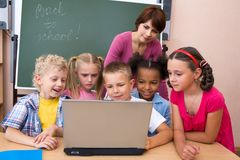 Teamwork. Portrait of pupils looking the laptop with teacher near by Stock Photography