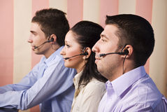 Teamwork. Three people customer service representative working in office , looking screen and standing in profile ,vertical blinds background.Check also,for Royalty Free Stock Photography