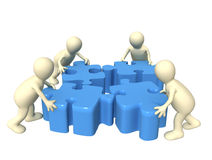 Teamwork. Four puppets, holding in hands a puzzle Royalty Free Stock Photos