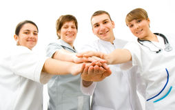 Teamwork. Team of young doctors a over white background, in focus the hands Royalty Free Stock Photography