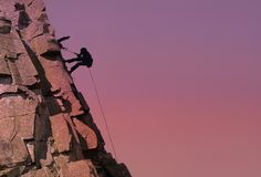 Teamwork. Silhouette against a stunning Sky with Two Climbers on Rockface with one abseiling down from ledge stock images
