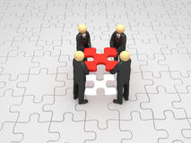 Teamwork. A 3d image of business group solving puzzle Royalty Free Stock Photos
