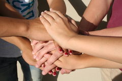 Teamwork. Team memebers stacking their hands as they go for a team salute Royalty Free Stock Image
