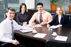 Teamwork. Four business colleagues sitting around table and working together, looking at camera, smiling stock image