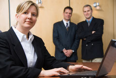Teamwork. 3 people looking at the camera with a laptop royalty free stock image