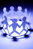 Teamwork. Paper cut-outs of people holding hands representing teamwork Royalty Free Stock Image