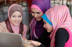 Teamwork. Young muslim women in head scarf using laptop in cafe with friends Stock Image
