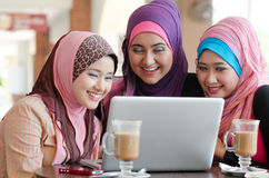 Teamwork. Young muslim women in head scarf using laptop in cafe with friends Stock Images