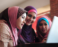 Teamwork. Young muslim women in head scarf using laptop in cafe with friends Royalty Free Stock Image