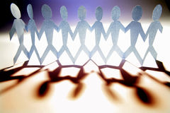 Teamwork. A line of paper people holding hands Royalty Free Stock Images