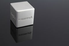 Teamwork. Metal paperweight with the word teamwork resting on a glass table Stock Photos