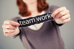 Teamwork. A business concept about teamwork - a female holding two pieces of paper with the words team and work which are sown together Stock Photos