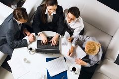 Teamwork. Three businesswomen and a businessman sitting on the white sofas at the round table with opened laptop, documents and cups of coffee on it and