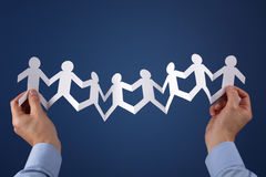 Teamwork. Concept with paper chain group of people holding hands held over blue background Royalty Free Stock Image