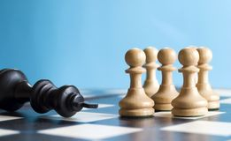 Teamwork. Team of pawns defeats the king in a game of chess Stock Photography