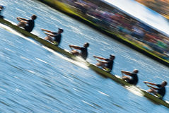 Teamwork. Speeding rowing boat with motion blur to accent speed Stock Photography