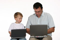 Teamwork. Father and toddler son sitting both working on laptop computers royalty free stock photography