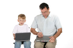 Teamwork. Father and toddler son both working on laptop computers stock photos