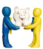 Teamwork. Two plasticine businessmen hold piggy bank stock images