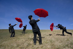Teamwork. Four businessman with red umbrellas on the nature stock photos