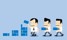 Teamwork; Affärsmän som tillsammans hjälper att avsluta uppgift Royaltyfri Bild