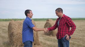 Teamwork agriculture smart farming concept. two men farmers business having firm friendly handshake workers shake hands. Studying haystack in field on digital stock video