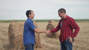 Teamwork agriculture smart farming concept. Two men farmers business having firm friendly handshake workers shake hands. Studying haystack in field on digital stock video footage