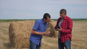 Teamwork agriculture smart farming concept. two men farmers workers studying lifestyle a haystack in a field on digital stock video