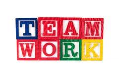 Teamwork - alfabetet behandla som ett barn kvarter på vit Royaltyfri Fotografi