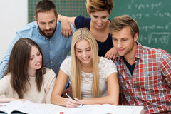 Teamwork amongst students. With a diverse group of young men and women crowded together behind a desk in the classroom working on a project sharing ideas and Royalty Free Stock Photo