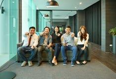 Teamwork av asiatiskt affärsfolk som sitter på soffan i vardagsrum royaltyfri foto