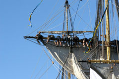 Teamwork on boat. Sailors hanging from sail-rigg Stock Image