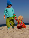 Teamwork. Boy and girl playing in the sand/ at the beach Stock Photo