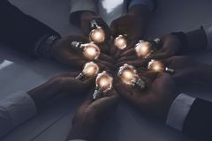 Teamwork and brainstorming concept with businessmen that share an idea with a lamp. Concept of startup. Teamwork and brainstorming concept with businessmen that royalty free stock photos