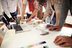 Teamwork,brainstorming concept.Young creative managers team working with new startup project in modern office. Contemporary notebook on wood table.Horizontal stock photography