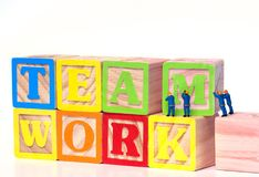 Teamwork Building Blocks. Teamwork - Miniature construction worker figurines posed as if building the word Teamwork with toy blocks royalty free stock images