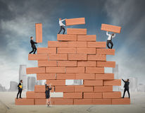 Teamwork builds a new business. Business person built together a big brick wall stock photo