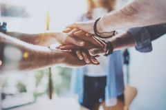 Teamwork business concept.Close up view of group of three coworkers join hand together during their meeting. Horizontal. Blurred background Stock Image