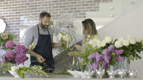 Teamwork business of two professional florists working at flower shop. Teamwork business at flower shop stock footage