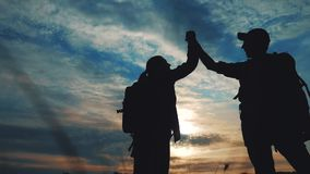 Teamwork business journey concept win. happy family team tourists man and woman sunset silhouette help shake hands. Victory success . slow motion video. tourism stock footage