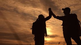 Teamwork business journey concept win. happy family team tourists man and woman sunset silhouette help shake hands. Victory success . slow motion video. tourism stock video