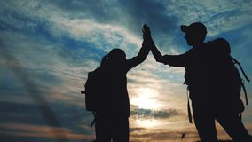 Teamwork business journey concept win. Happy family team tourists man and woman sunset silhouette help shake hands stock footage