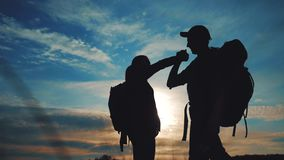 Teamwork business journey concept win. team tourists man and woman sunset silhouette help shake hands success victory. Lifestyle slow motion video. tourism stock video